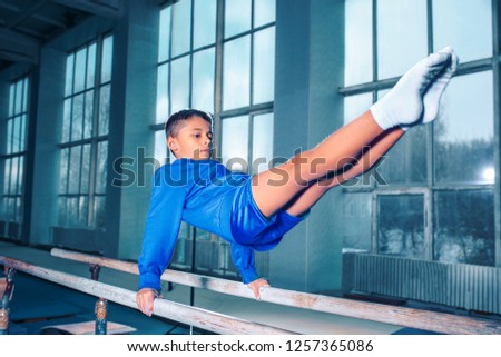 The little boy is engaged in sports gymnastics on a parallel bars at gym. The performance, sport, acrobat, acrobatic, exercise, training concept