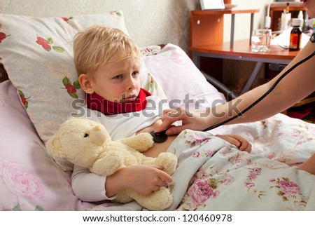 The little boy is sick. He lies in bed. Red scarf is on his neck. Teddy Bear is in his hand. Woman explores boy's lungs with a stethoscope. - stock photo
