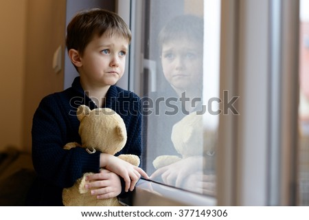 Shutterstock The little boy looks out the window. Rainy Day. Loneliness and waiting concept