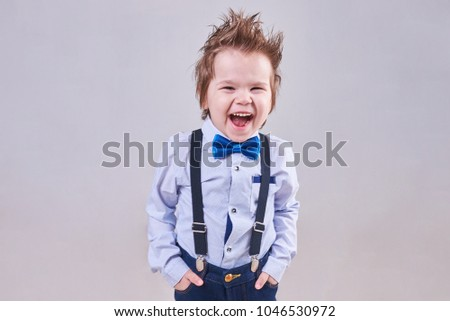 The little boy screams and smiles in a blue bow tie and suspenders