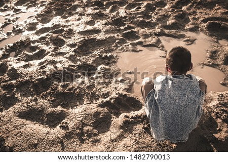 The little boy waiting for drinking water to live through this drought, Concept drought and crisis environment.