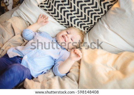 The little boy with blond hair lying on pillows with bright bed and smiling with a children's room #598148408