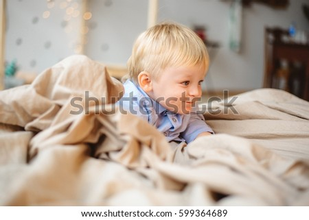 The little boy with blond hair lying on pillows with bright bed and smiling with a children's room #599364689