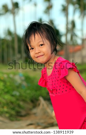 The little carefree Vietnamese girl smiles - stock photo