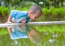 The little child plays with his self reflection in a small pond.