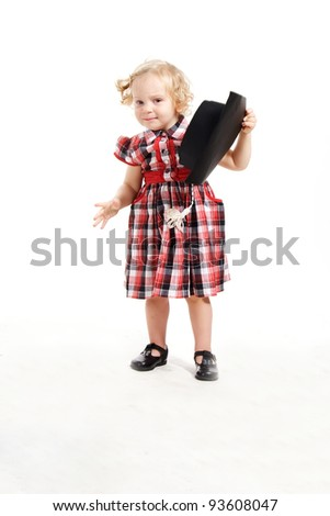 The little curly-haired blonde girl, wearing a checkered dress and graduation cap learning to walk