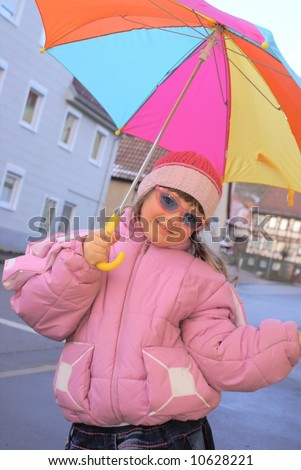 The little girl a pink jacket and pink children's sun glasses, with an umbrella in his hand .It is under colorful umbrella, it was dressed in winter clothes.
