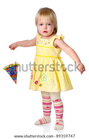 The little girl costs with a party hat in a hand. Isolated on a white background