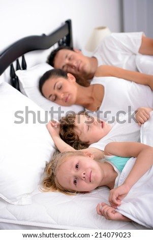 The little girl crying in bed at the time when the mother, father and brother sleep in the bedroom
