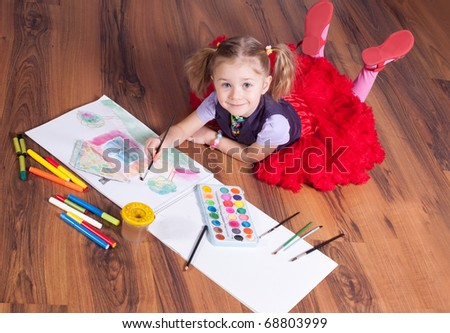 The little girl draws on a floor