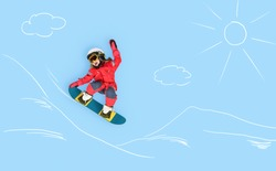 The little girl dreaming about winter season and snowboarding. Childhood and dream concept. Conceptual image with girl who conquers slopes on a snowboard. Dreams about sports.