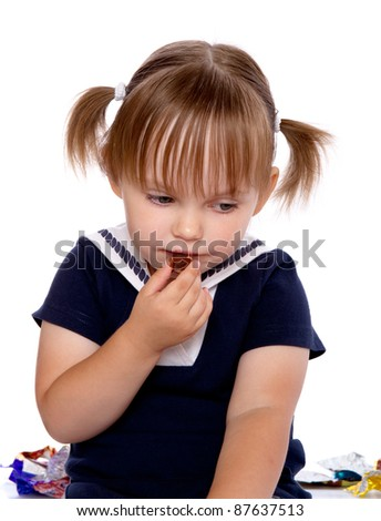 The little girl eats a chocolate. Isolated on a white background
