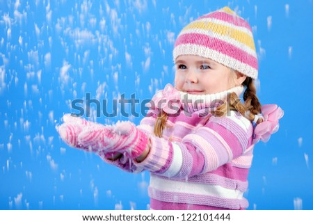 the little girl in a sweater and a hat with the snow