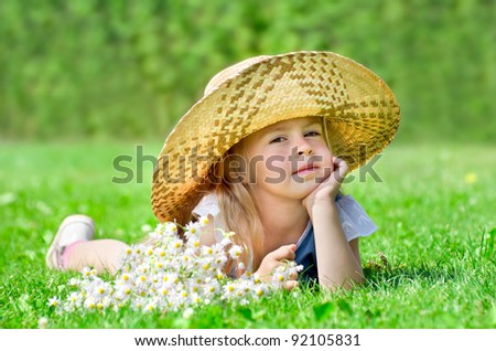 The little girl in hat lying on the lawn