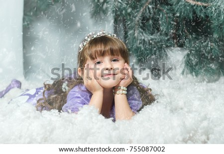 The little girl in the snow against a backdrop of spruce, Studio photoshoot. new year2018, New Year's decorations