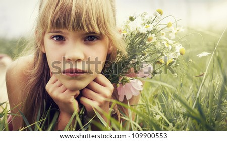 The little girl is lying in the meadow and holding the bouquet