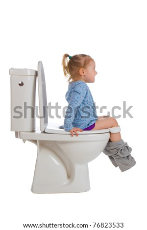 the little girl is sitting on toilet