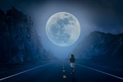 The little girl is walking on the dark carriage at night, watching the full moon rise.