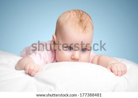 the little girl lies on a pillow - cloud. on a blue background.
