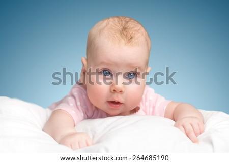 the little girl lies on a pillow - cloud. on a blue background