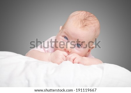 the little girl lies on a pillow - cloud. on a gray background.