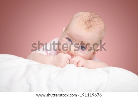 the little girl lies on a pillow - cloud. on a pink background.