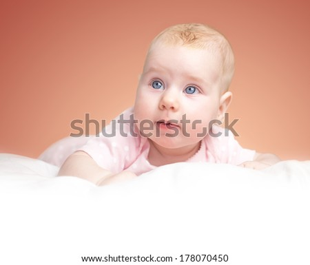 the little girl lies on a pillow - cloud. on a pink background. white place with a bottom for your text