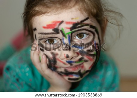 The little girl painted her face with crayons.-Children's mischief Stock photo ©