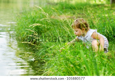The little girl playing park near the lake