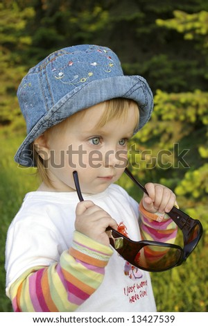 The little girl plays with glasses on a background of the nature