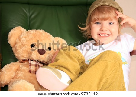 The little girl poses in the big green leather armchair with a toy bear