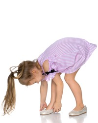 The little girl puts on her shoes. The concept of beauty and fashion, happy childhood. Isolated on white background.