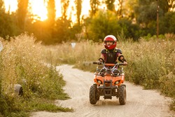 The little girl rides a quad bike ATV. A mini quad bike is a cool girl in a helmet and protective clothing. Electric quad bike electric car for children popularizes green technology.