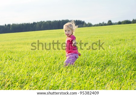 The little girl runs across the field on a decline