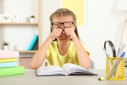 The little girl's eyes hurt from her glasses. Vision problems in children, vision correction and examination.