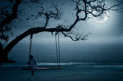 The little girl sits at the seaside swings on a full moon night like a lonely nature.