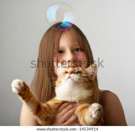 The little girl sits, holds a red cat, and it catches soap bubbles