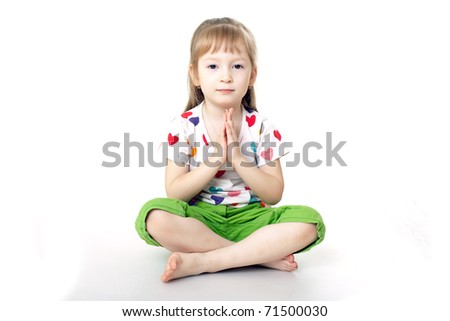 The little girl sits in a pose meditation