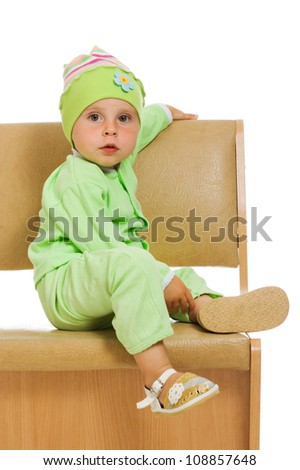 The little girl sits on a high chair isolated on a white background