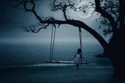 The little girl sits on the seaside swing on a full moon night.