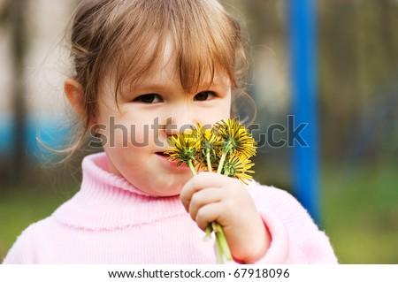 The little girl smells flowers
