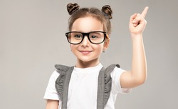 The little girl smiles and shows her index finger up. A child with glasses happily instructs and teaches or explains something. Happy childhood. Expressive facial emotions