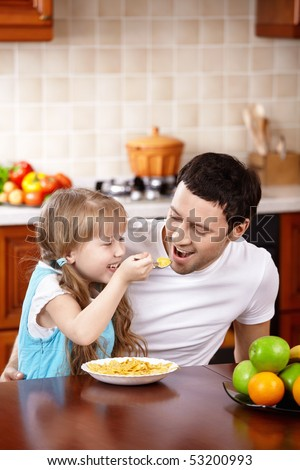 The little girl spoon-feeds the daddy on kitchen