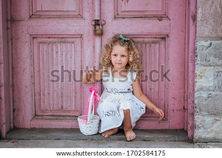 The little girl stays in front of pink house. Background made of a colorful old house. Vintage style