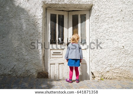 The little girl was staring at the old door in the street