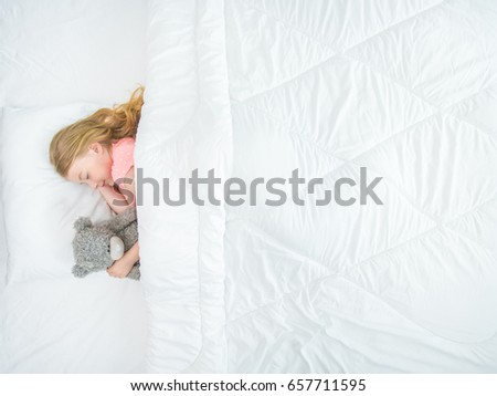 The little girl with a soft toy sleeping on the bed. view from above