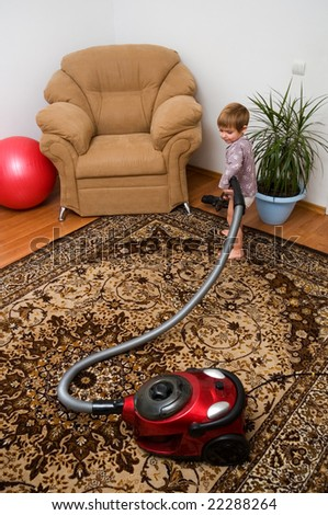 The little girl with a vacuum cleaner helps at home