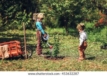 The little girls gardener playing in garden.
