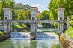 The Ljubljanica River Barrier and the city castle at the background in Ljubljana, Slovenia's capital. The barrier is a sluice gate and a triumphal arch by the architect Jože Plečnik.