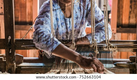 The local Intha woman weaving the lotus cloth with the hand loom at the local lotus cloth weaving factory in Inle lake, Shan State, Myanmar. Selective focused